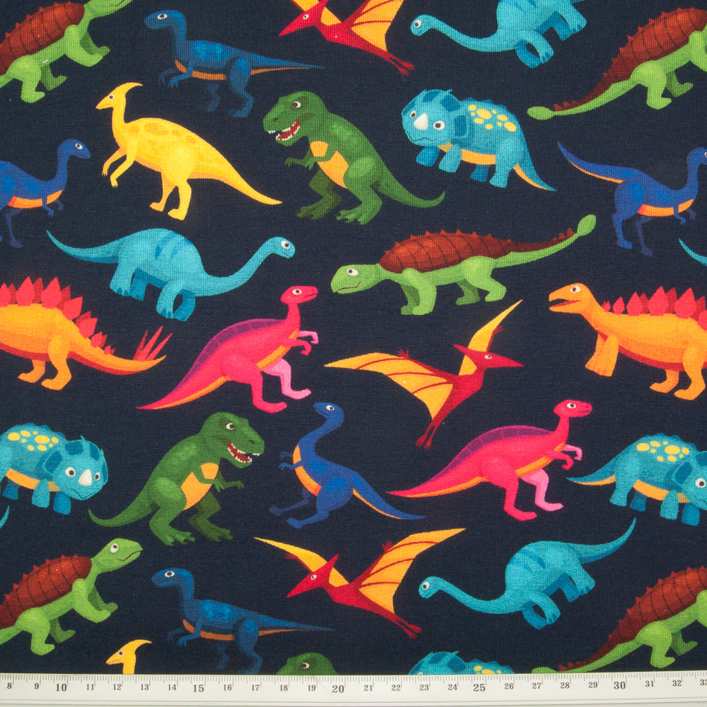 Various dinosaurs in green, pink, blue and yellow printed on a fat quarter piece of cotton jersey fabric on a navy background with a ruler for size perspective