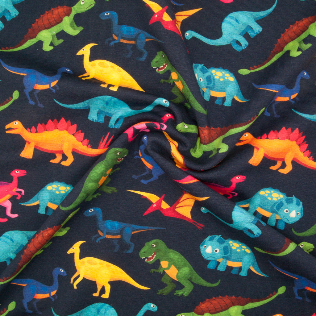 Various dinosaurs in green, pink, blue and yellow printed on a fat quarter piece of cotton jersey fabric on a navy background in a swirl for drape perspective