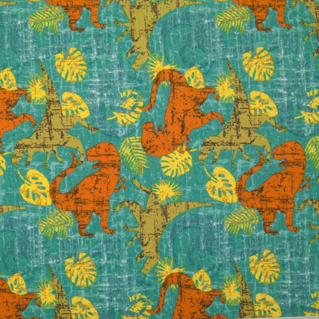 A fat quarter of cotton jersey fabric printed with green and terracotta dinosaurs in a jungle setting