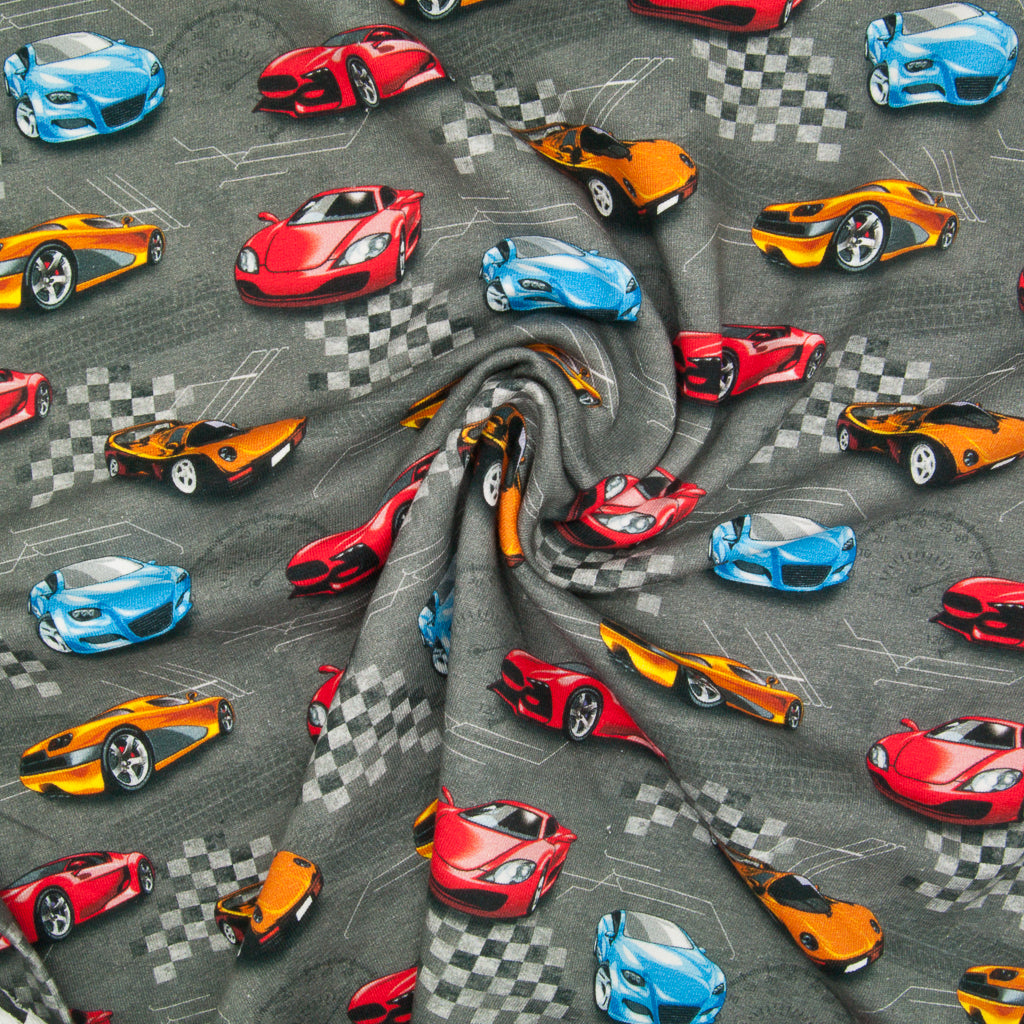 Yellow, blue and red racing cars are printed on a fat quarter of grey french terry cotton jersey fabric in a swirl for drape perspective