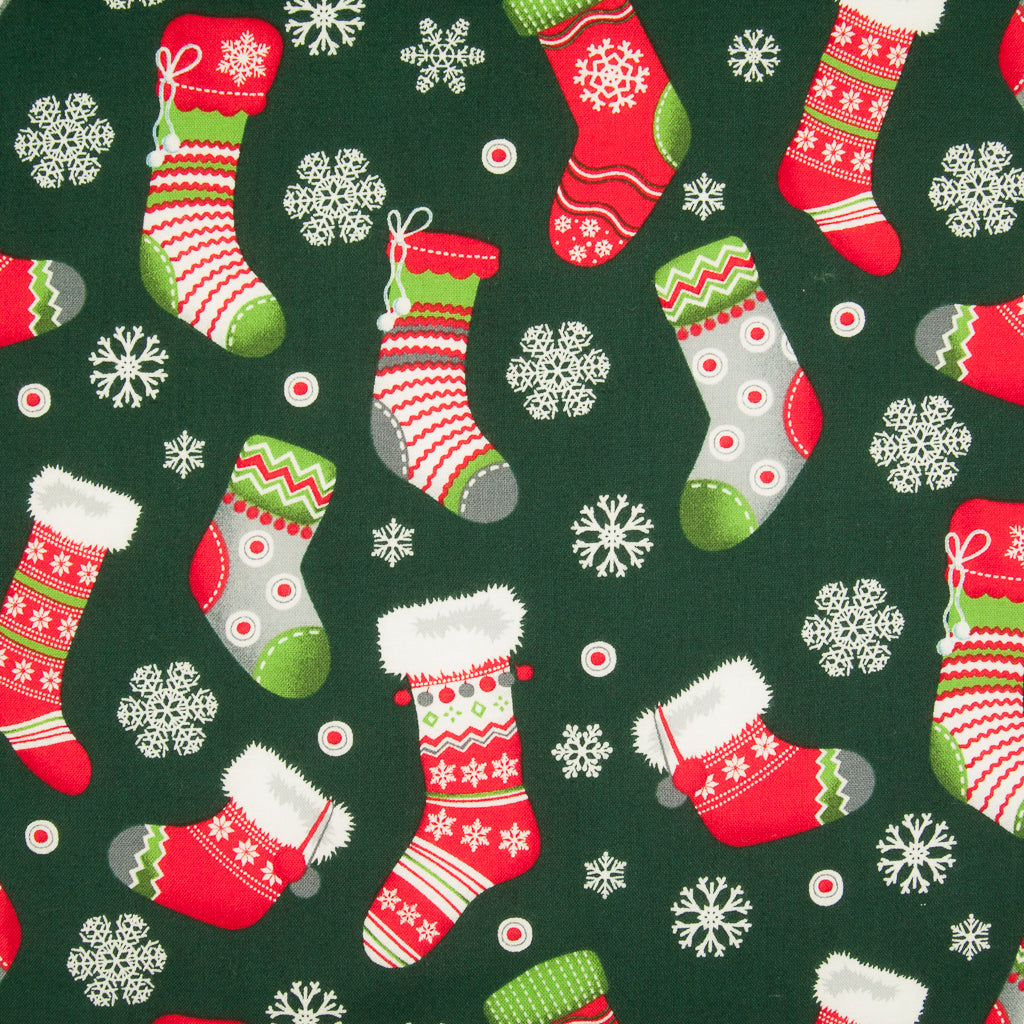 A Rose & Hubble Green Christmas cotton fabric featuring printed bright striped, spotty red, white, green stockings and snowflakes