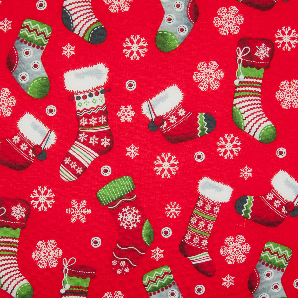 A Rose & Hubble Red Christmas cotton fabric featuring printed bright striped, spotty red, white, green stockings and snowflakes