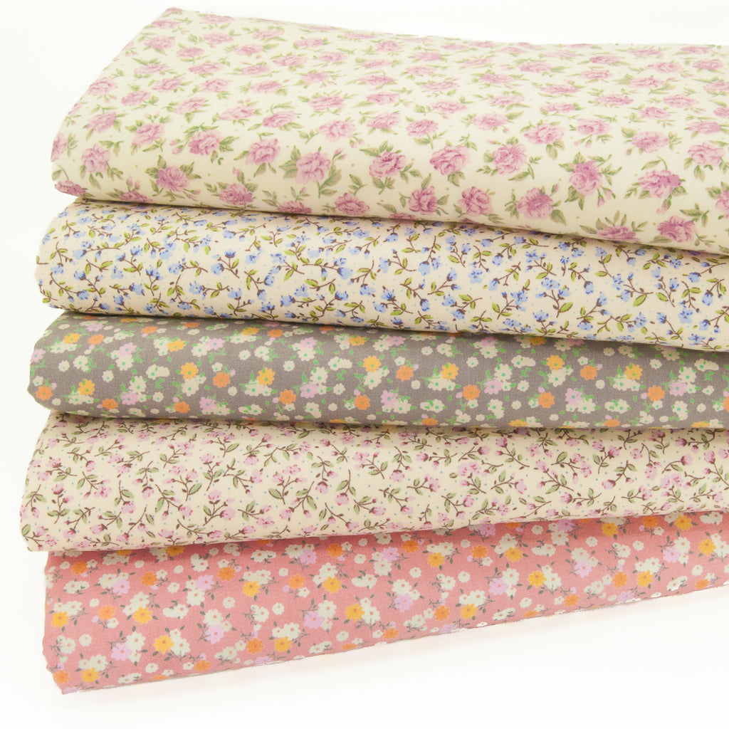Five pretty ditsy fabric prints in pink, lilac and taupe are arranged in a fat quarter bundle