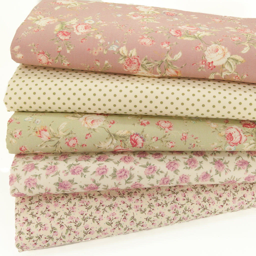 Five floral cotton fabrics in a bundle with a rose coloured design on top, a spot, a green rose and two ditsy designs
