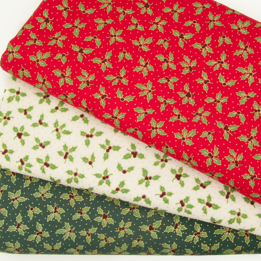 A fabric bundle of red, green and ivory christmas cottons printed with green and gold holly leaves in fan shape