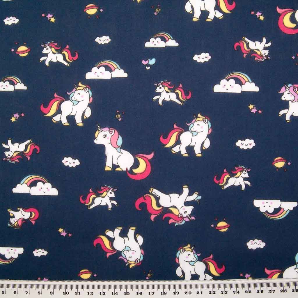 Cute white unicorns, colourful rainbows and stars are printed on a navy polycotton fabric with a ruler at bottom for size perspective