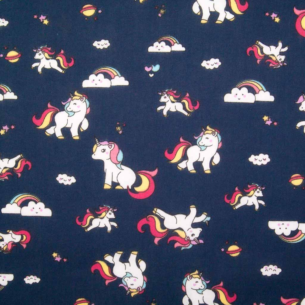 Cute white unicorns, colourful rainbows and stars are printed on a navy polycotton fabric