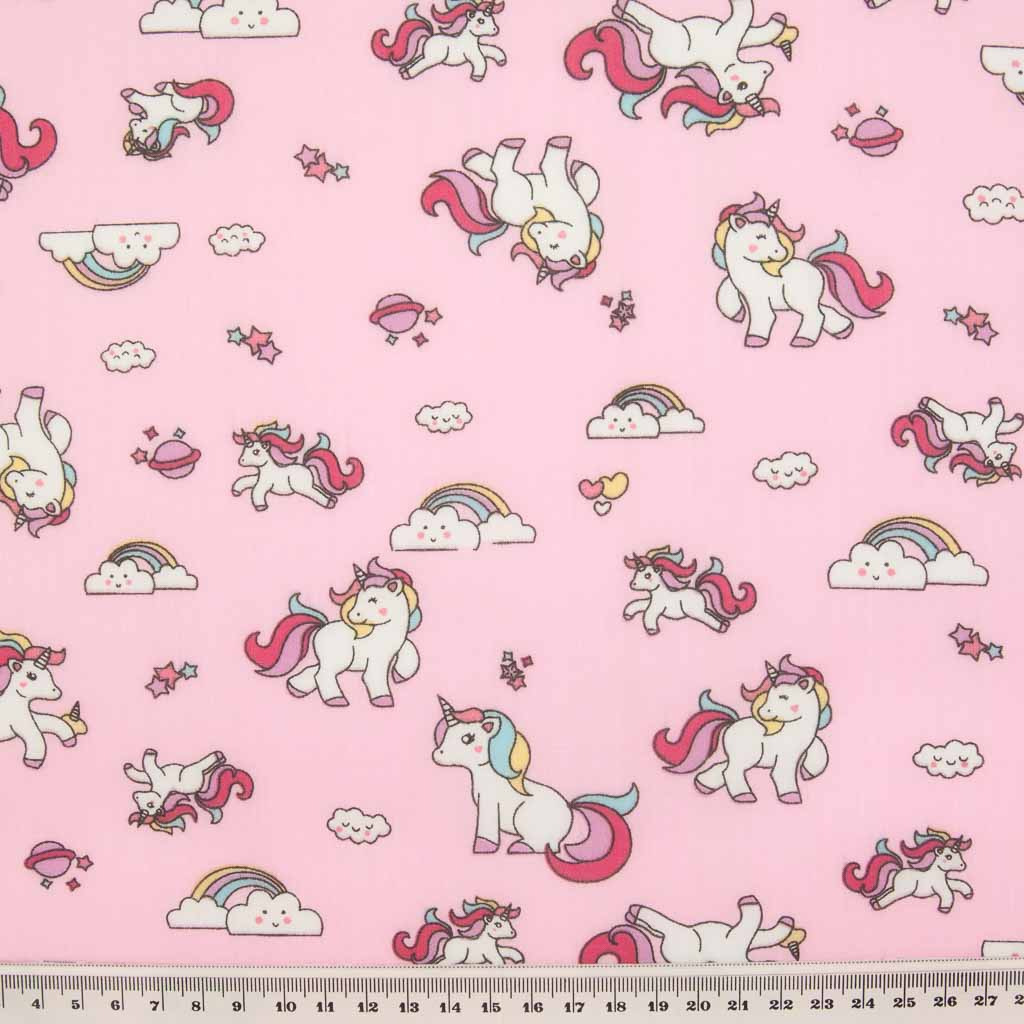 Cute white unicorns, colourful rainbows and stars are printed on a pink polycotton fabric with a ruler at the bottom for size perspective