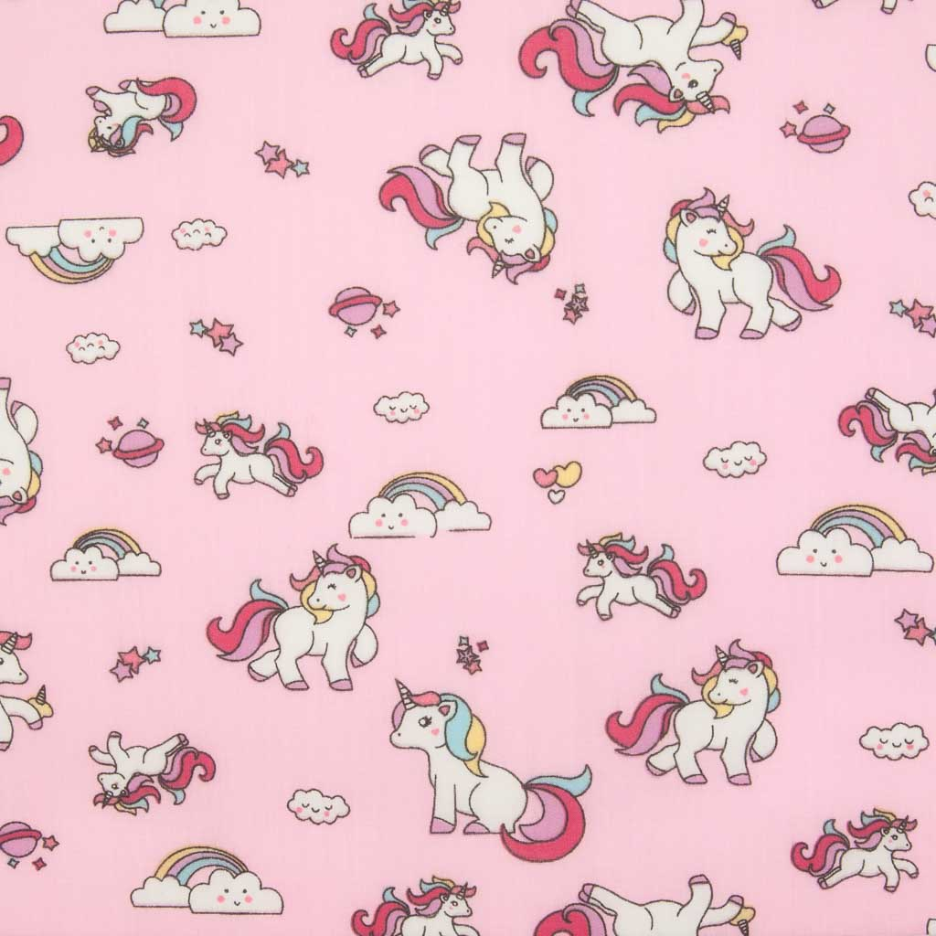 Cute white unicorns, colourful rainbows and stars are printed on a pink polycotton fabric