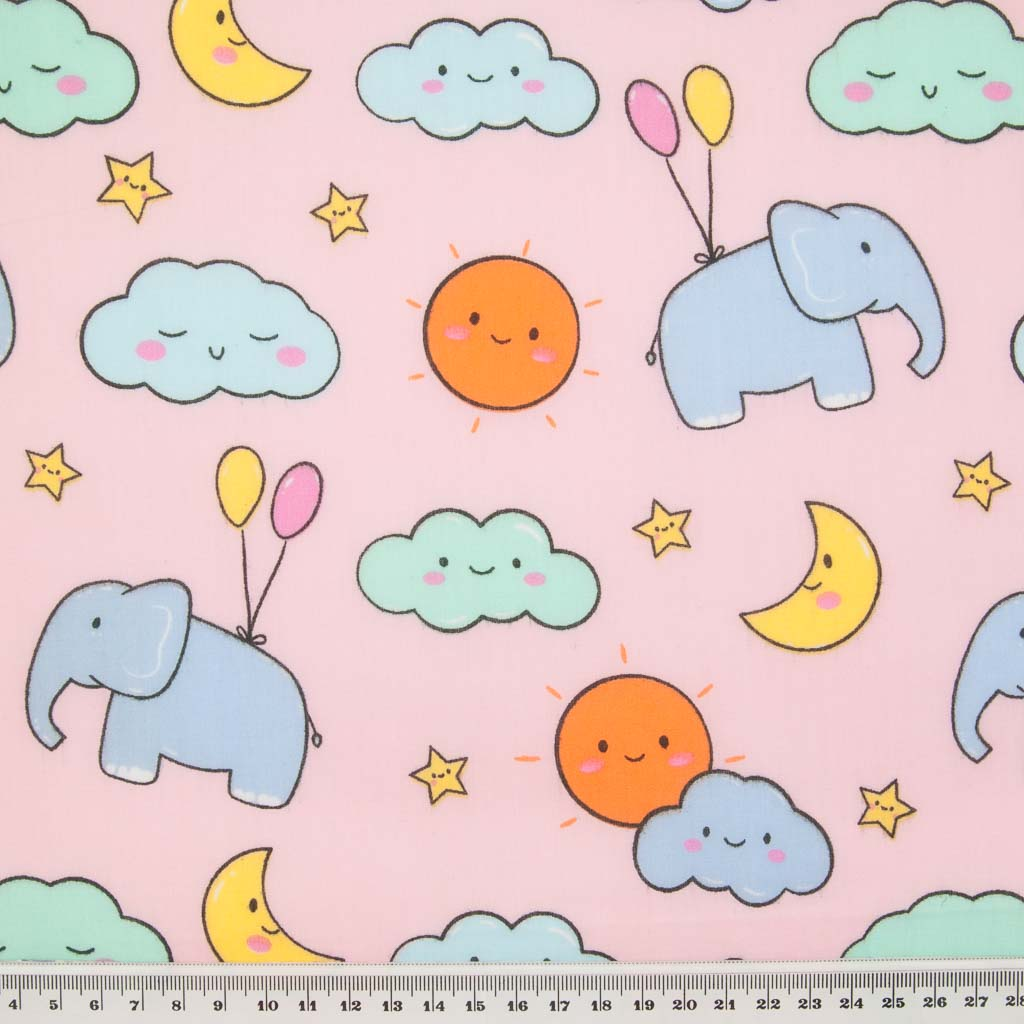 Blue elephants, pink and yellow balloons with orange sunshine and yellow moons printed on a pink polycotton fabric with a ruler for size perspective