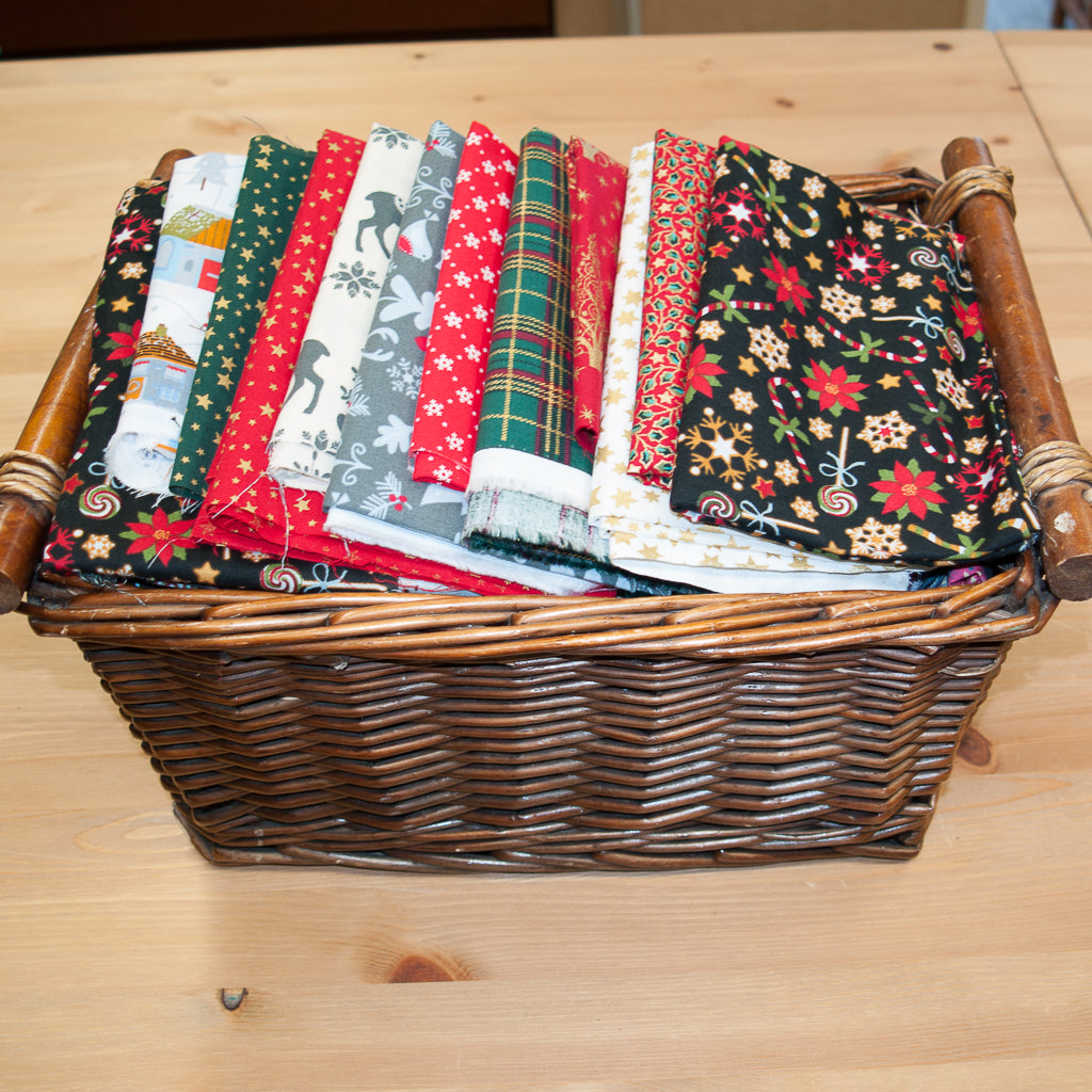 A wicker basket containing remnant pieces of christmas printed cotton fabric