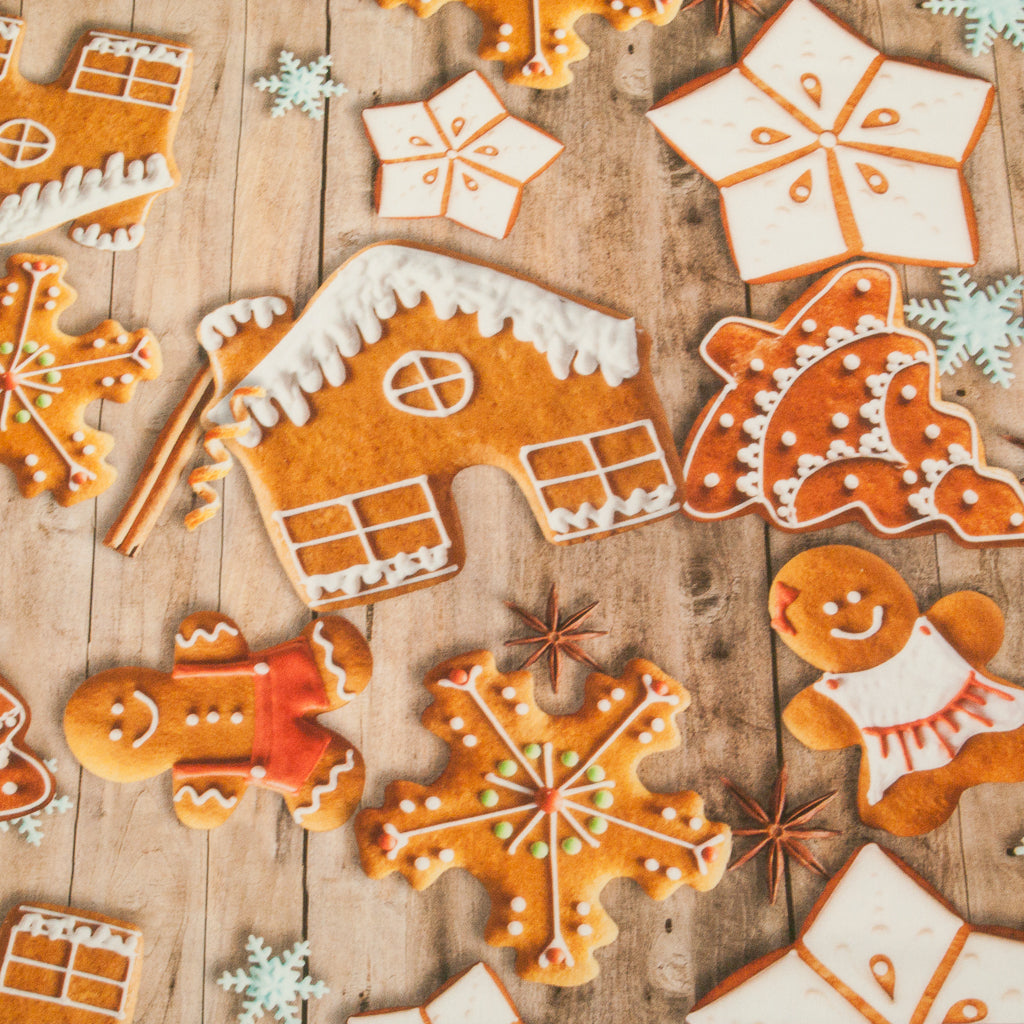 Cotton Fabric with a print of gingerbread houses, men and stars strewn on scandinavian wood