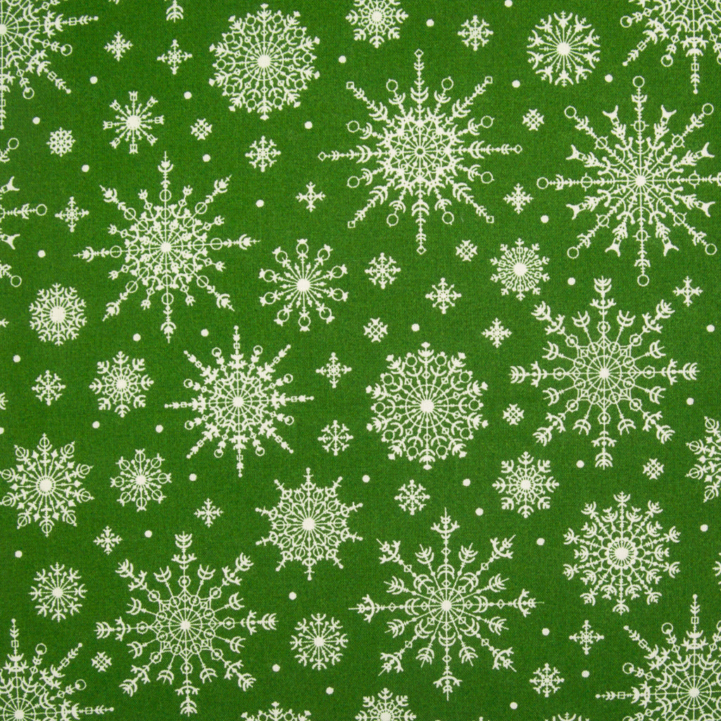White, intricately designed snowflakes in varying sizes printed on green cotton fabric