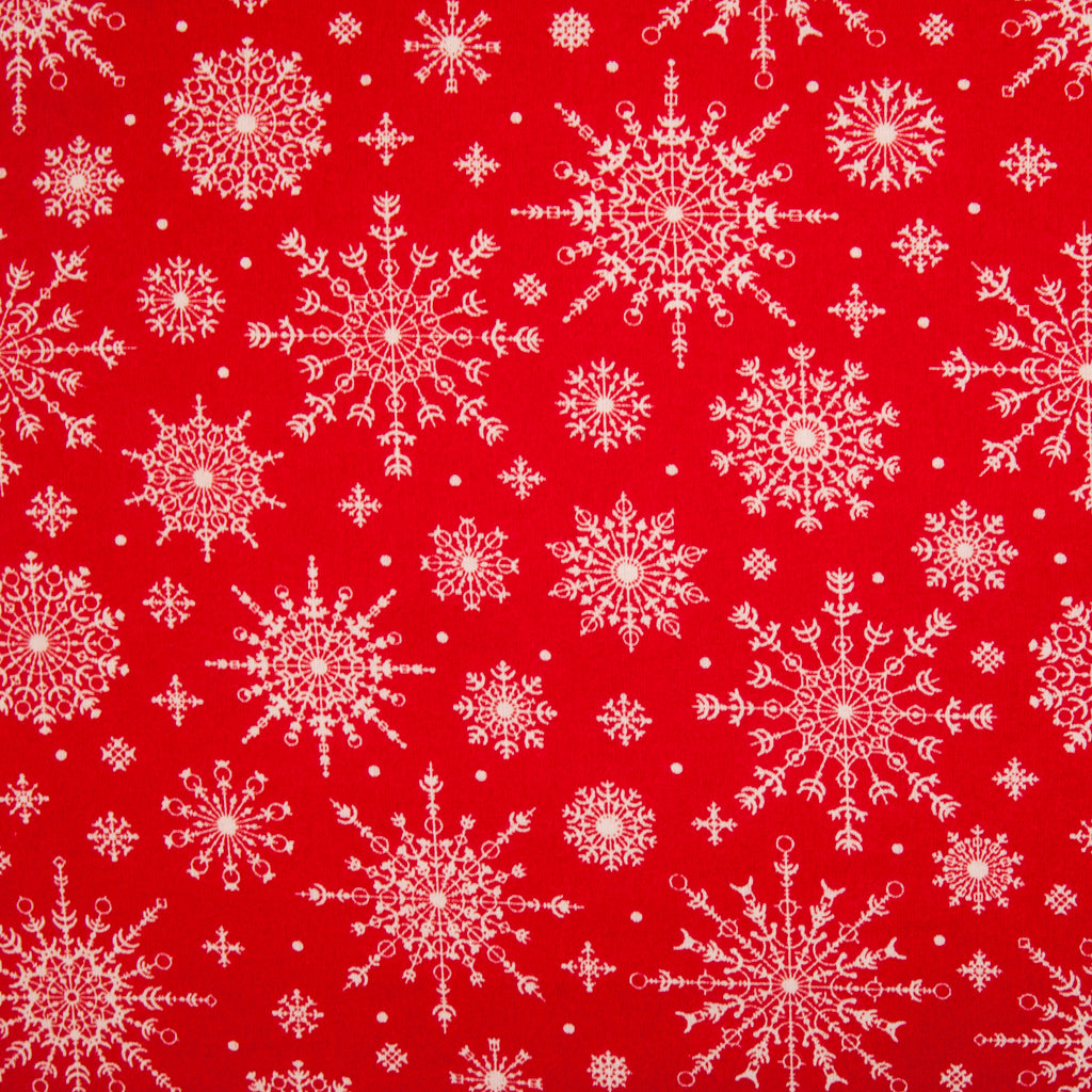 White, intricately designed snowflakes in varying sizes printed on red cotton fabric