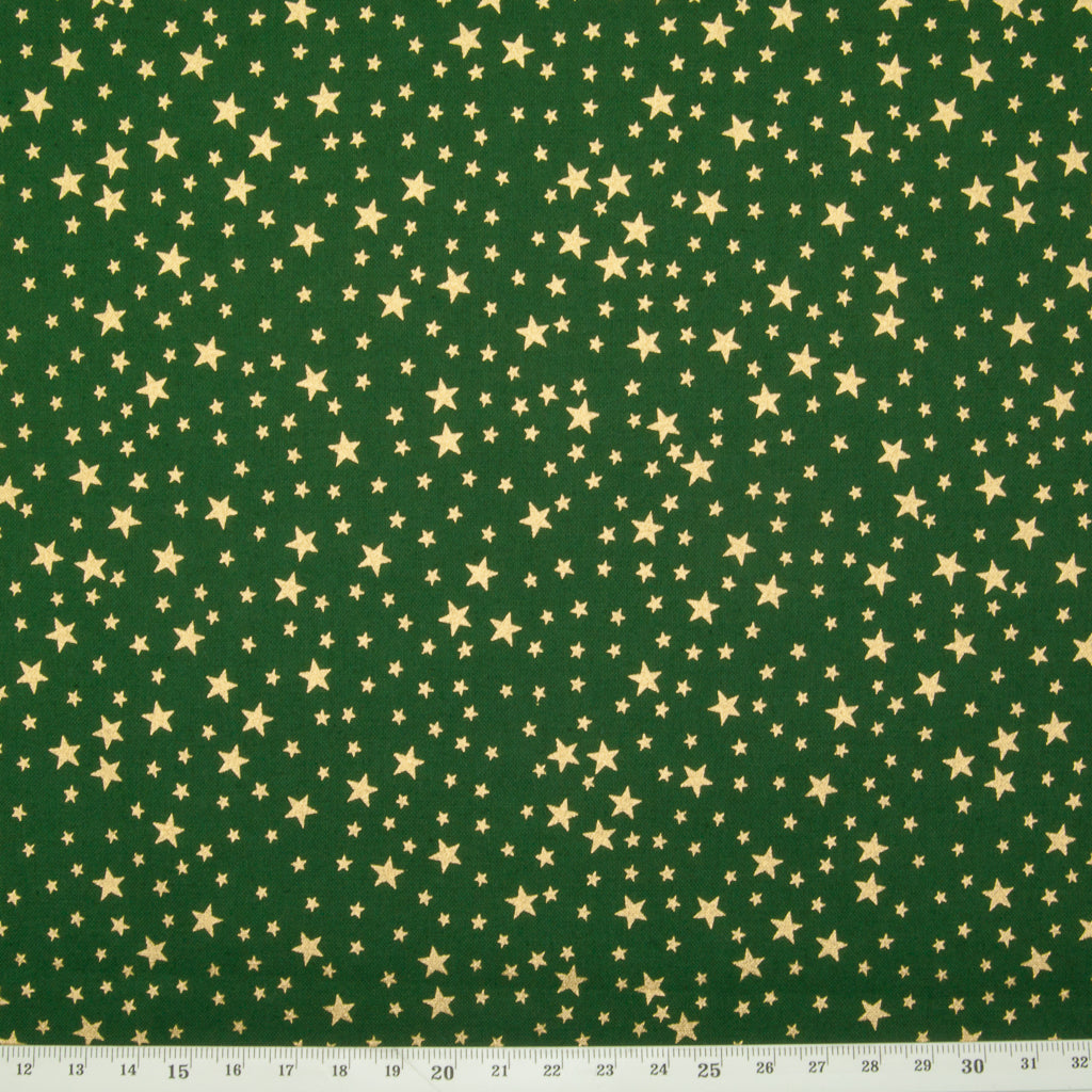 A green christmas cotton fabric featuring small metallic gold stars in a tossed pattern including a ruler for perspective