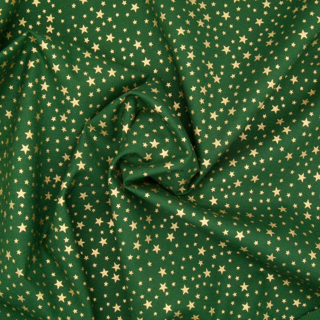A green christmas cotton fabric featuring small metallic gold stars in a tossed pattern in a decorative swirl