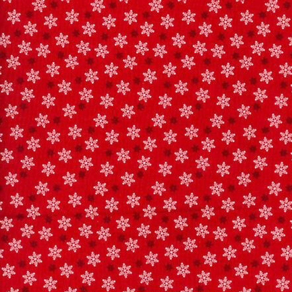 Small, white star shaped snowflakes on a red christmas cotton fabric in a tossed pattern