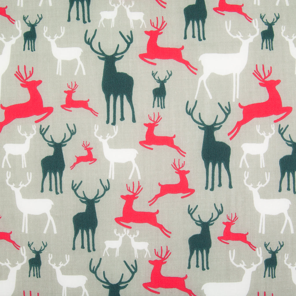 Christmas polycotton fabric in silver featuring printed stags or reindeer in red, green and white with antlers