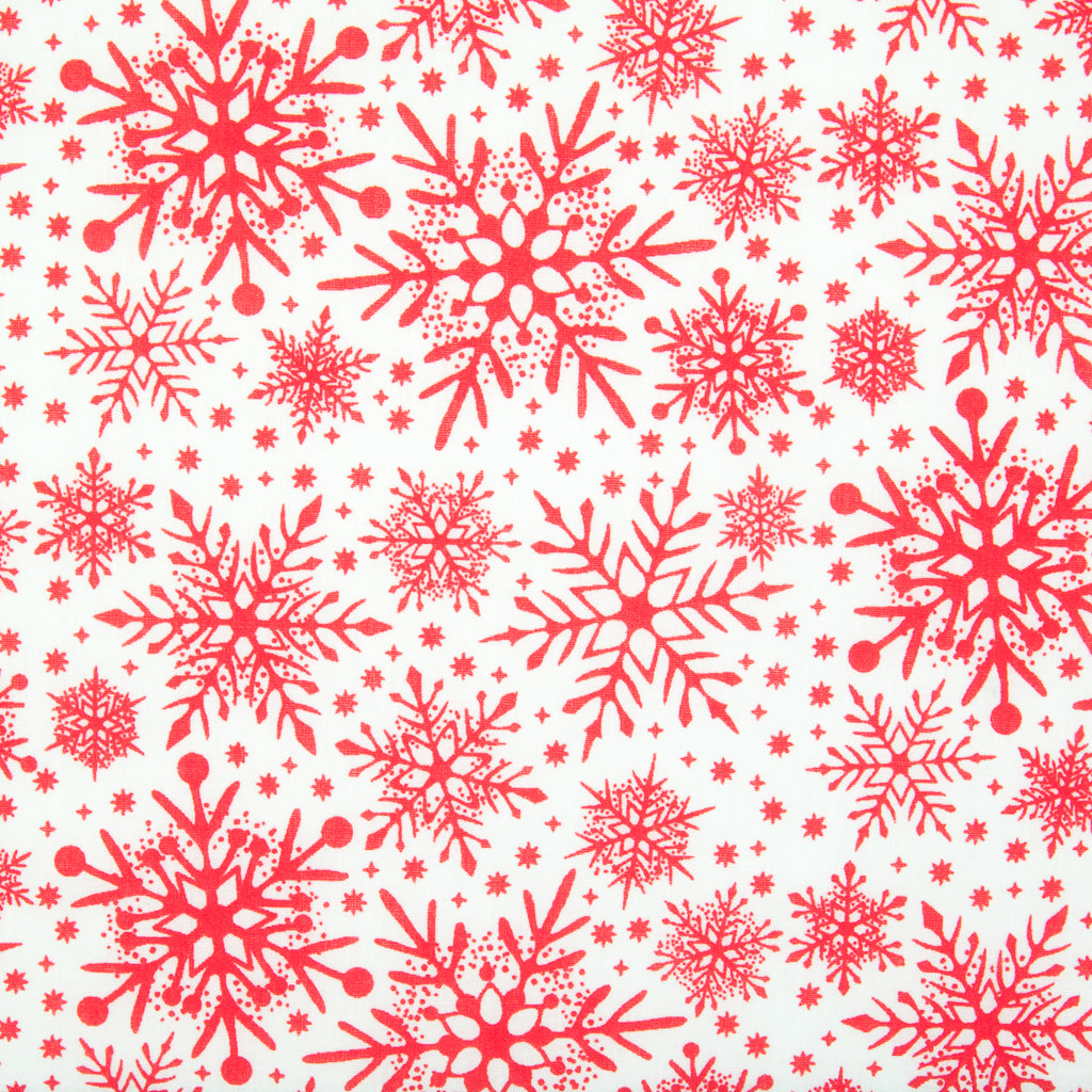 Varying sizes of intricate red snowflakes on a white christmas polycotton fabric