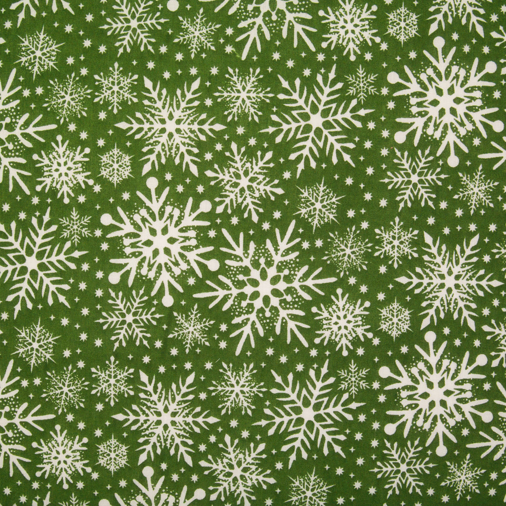 Varying sizes of intricate white snowflakes on a green christmas polycotton fabric