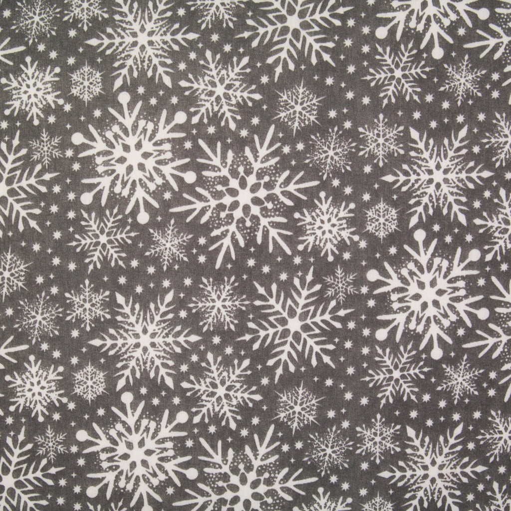 Varying sizes of intricate white snowflakes on a grey christmas polycotton fabric
