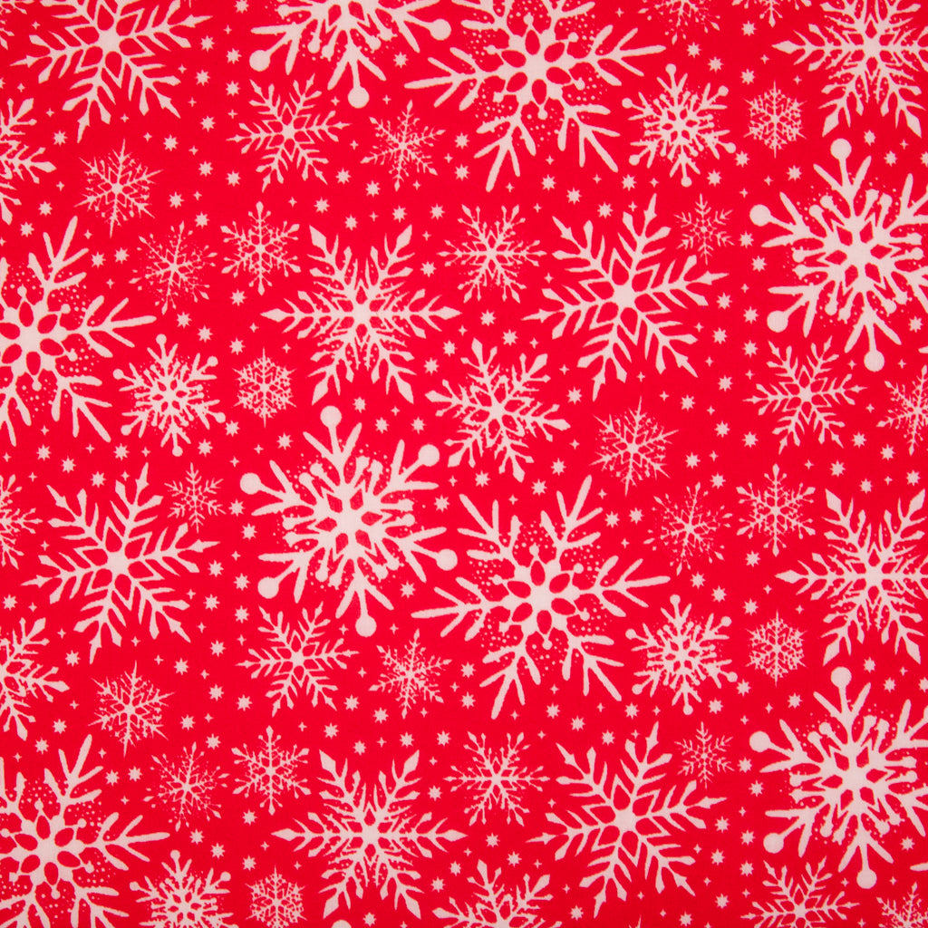 Varying sizes of intricate white snowflakes on a red christmas polycotton fabric