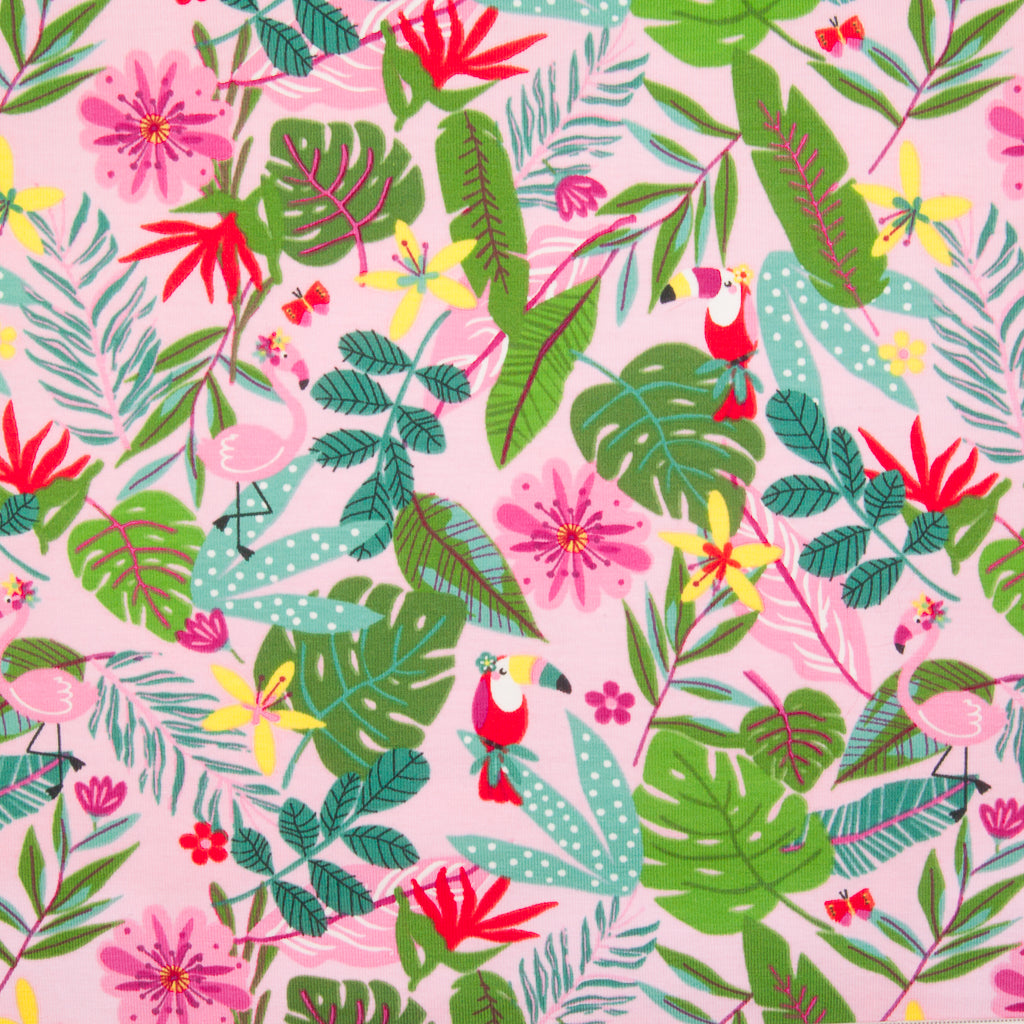 Many green palm leaves with red toucans and pink flamingos are printed on a pink jersey fabric