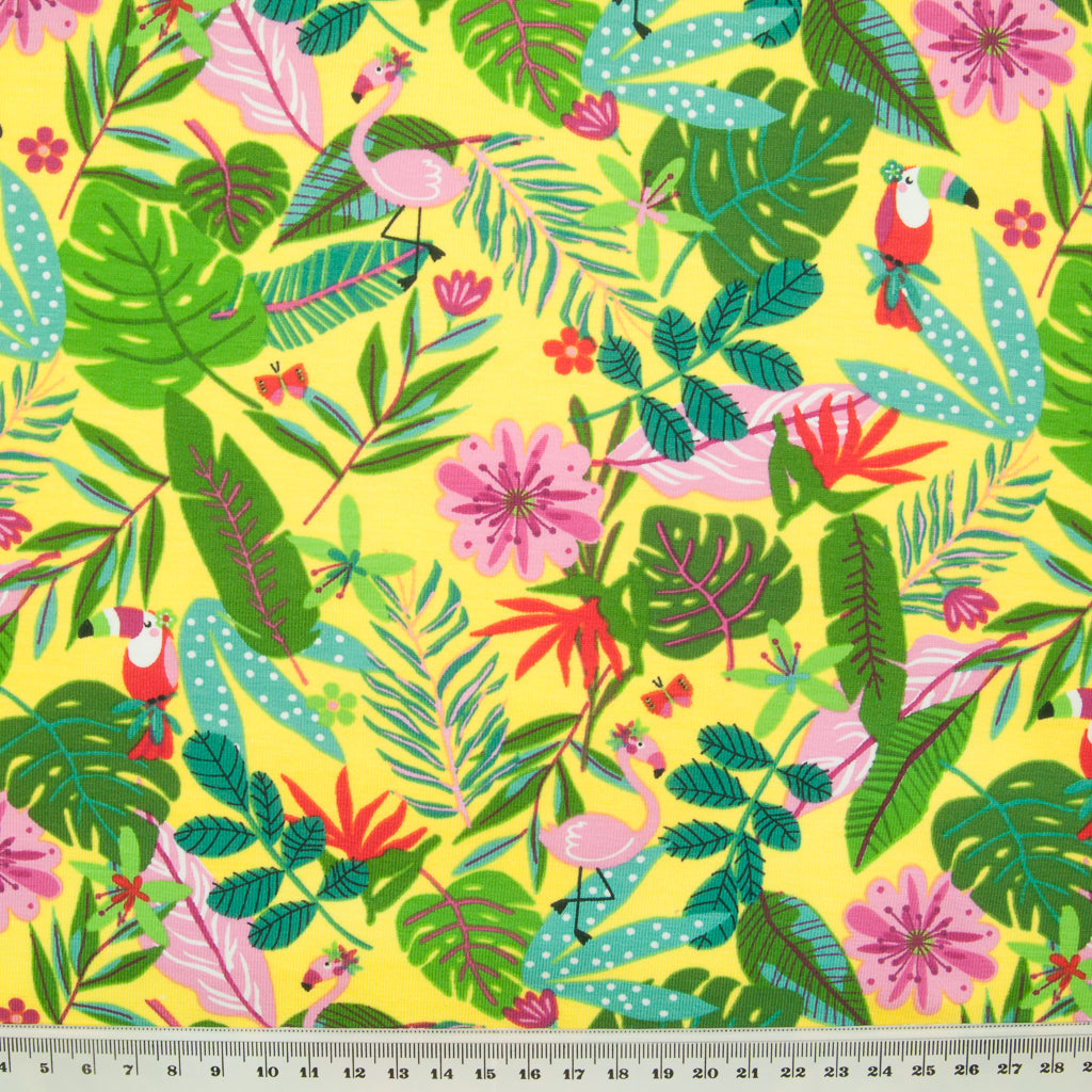 Many green palm leaves with red toucans and pink flamingos are printed on a yellow jersey fabric with a ruler at the bottom for size perspective