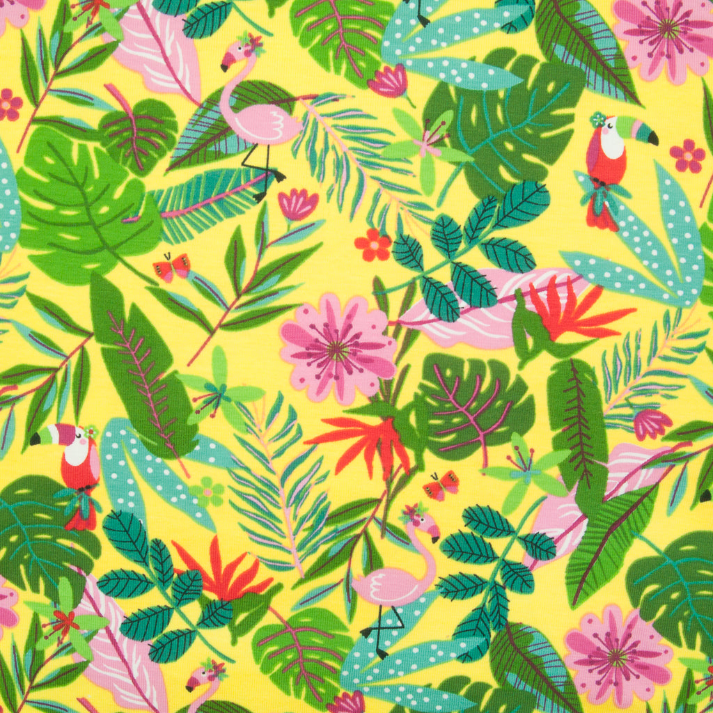 Many green palm leaves with red toucans and pink flamingos are printed on a yellow jersey fabric
