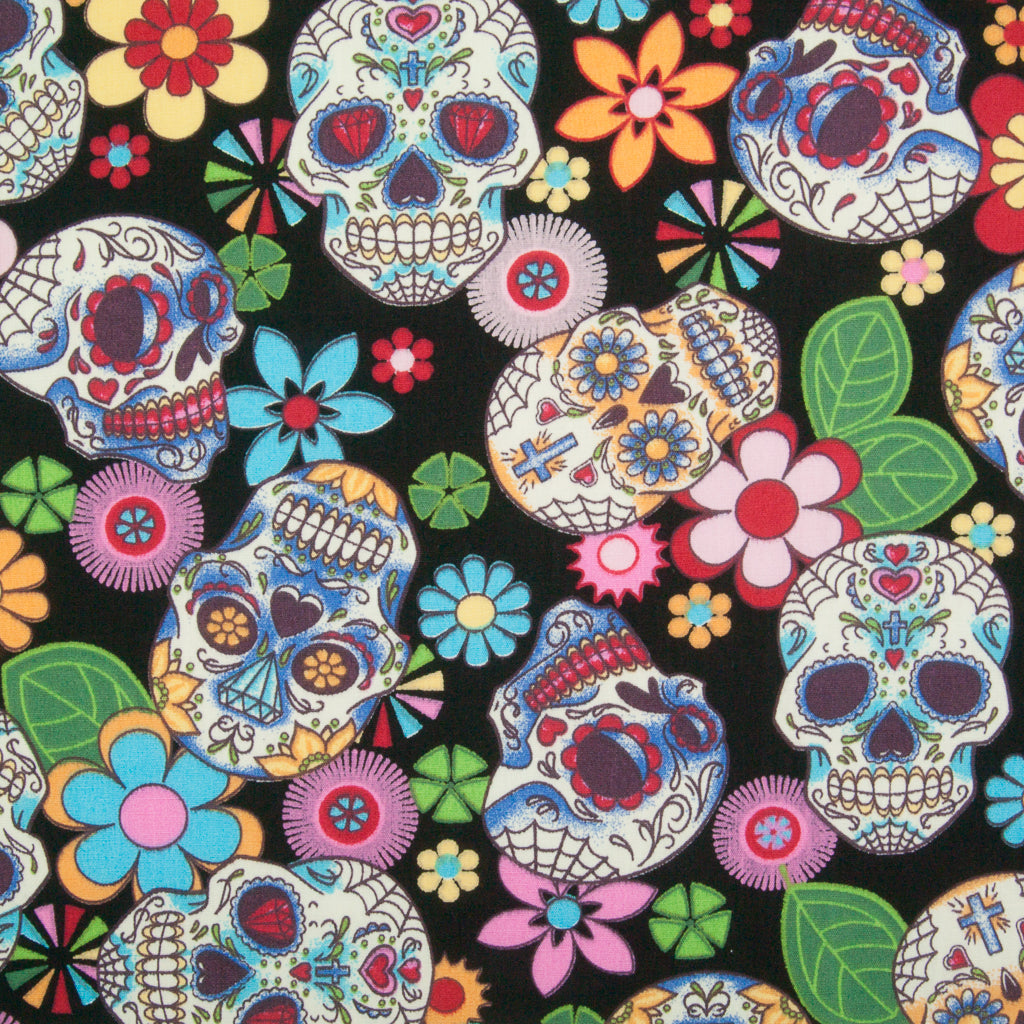 A Rose & Hubble cotton fabric with bright and colourful skulls and flowers printed on a black background