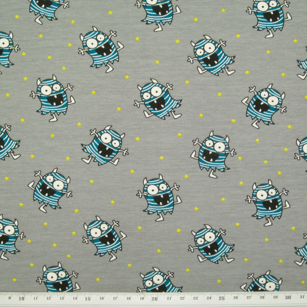 A fat quarter of grey cotton jersey fabric printed with turquoise aliens with large glow in the dark eyes with a ruler for size perspective