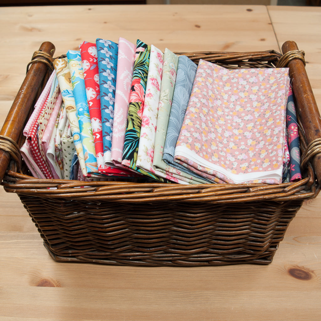 A wicker basket containing remnant pieces of floral printed cotton fabric