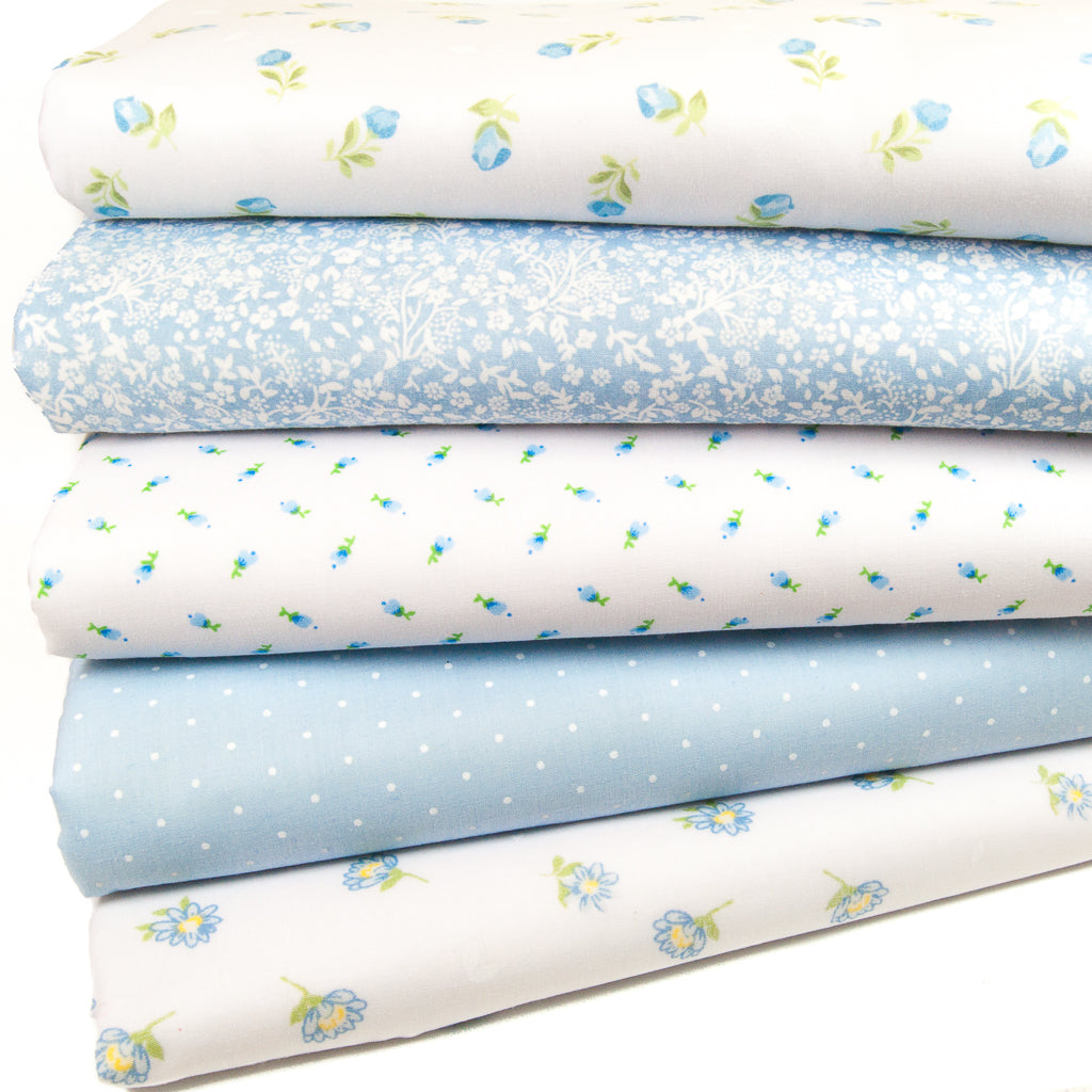Five blue polycotton floral fabric prints are arranged in a fat quarter bundle