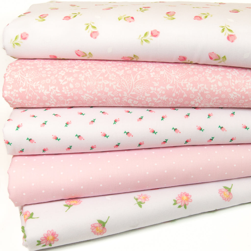 Five pink polycotton floral fabric prints are arranged in a fat quarter bundle