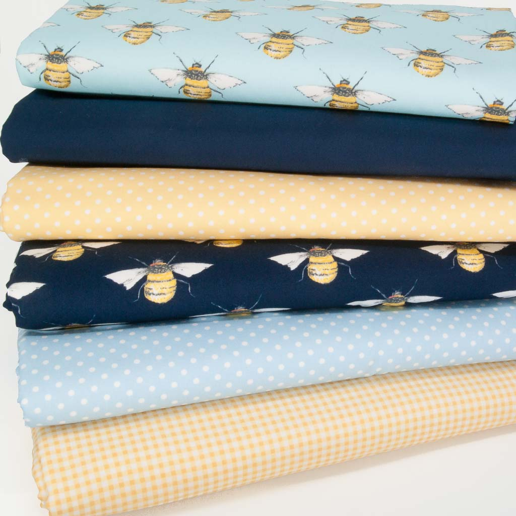 Six cotton fat quarters printed with bees, spot and checks on yellow and navy backgrounds
