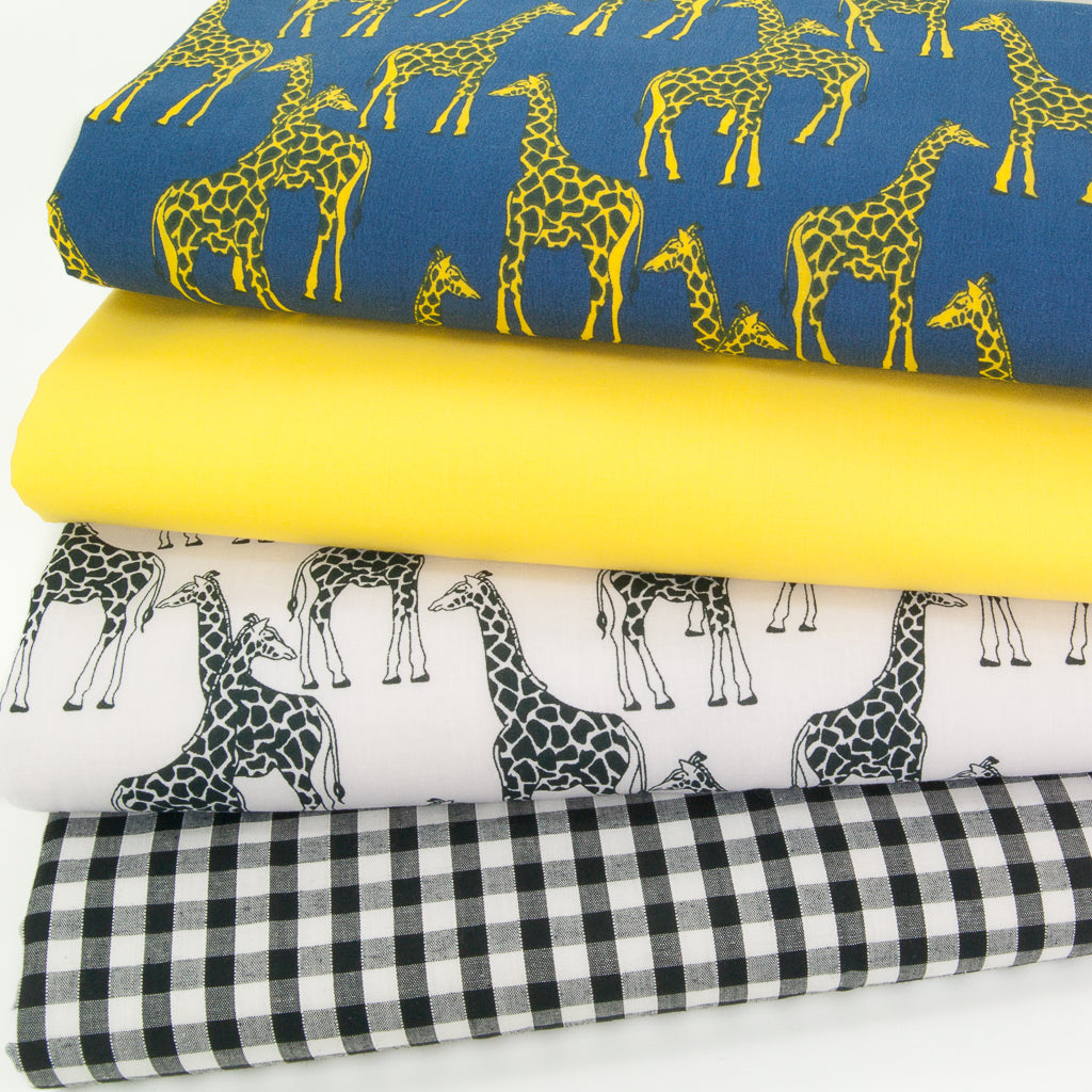 A fat quarter bundle of polycotton fabric prints showing yellow giraffes on a blue background and black and white giraffes