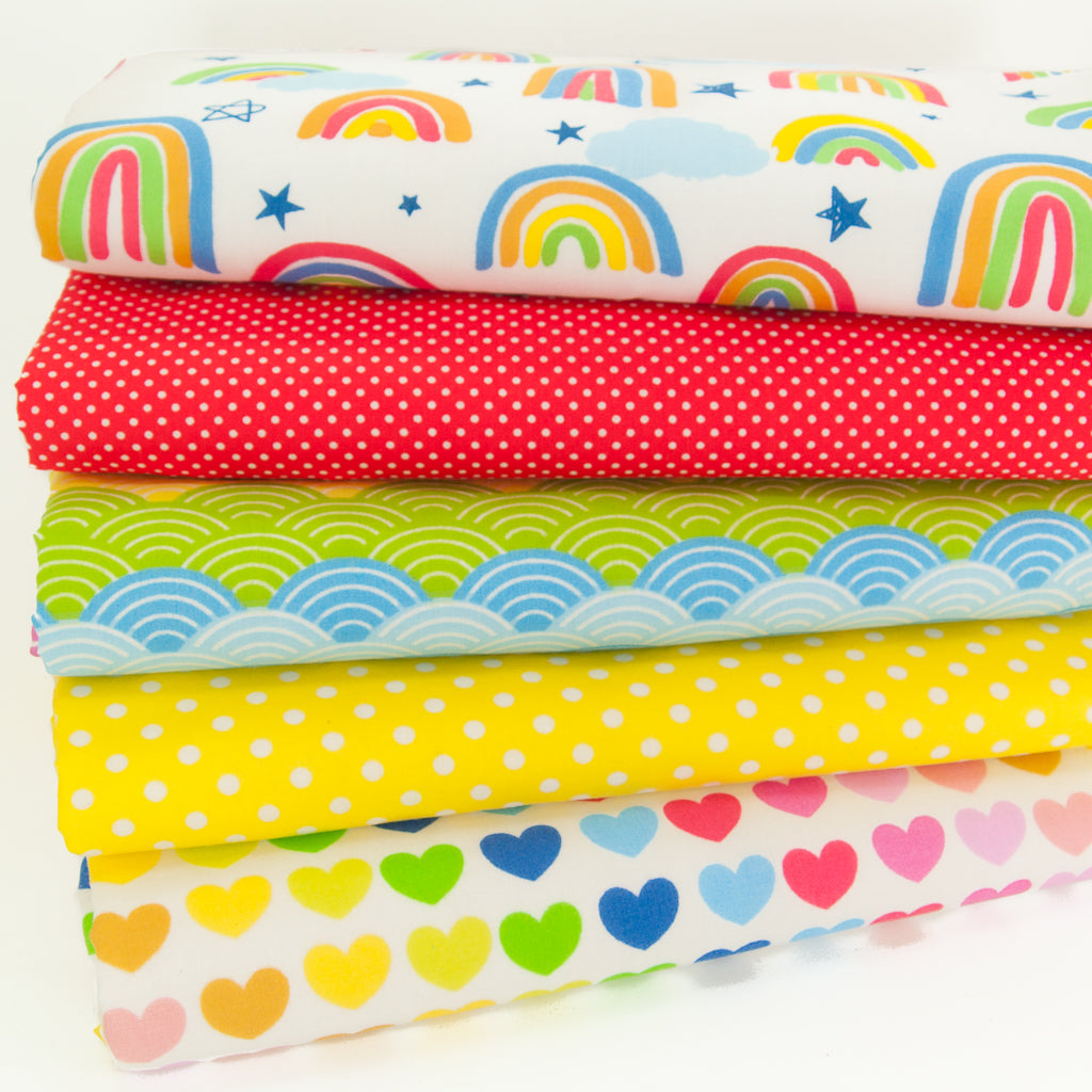 Five fabric fat quarters with rainbows, hearts and white spots arranged in a bundle