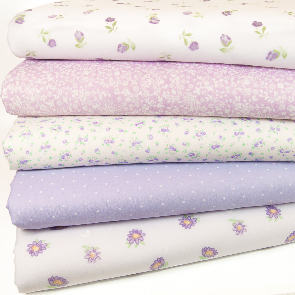 Five lilac polycotton floral fabric prints are arranged in a fat quarter bundle