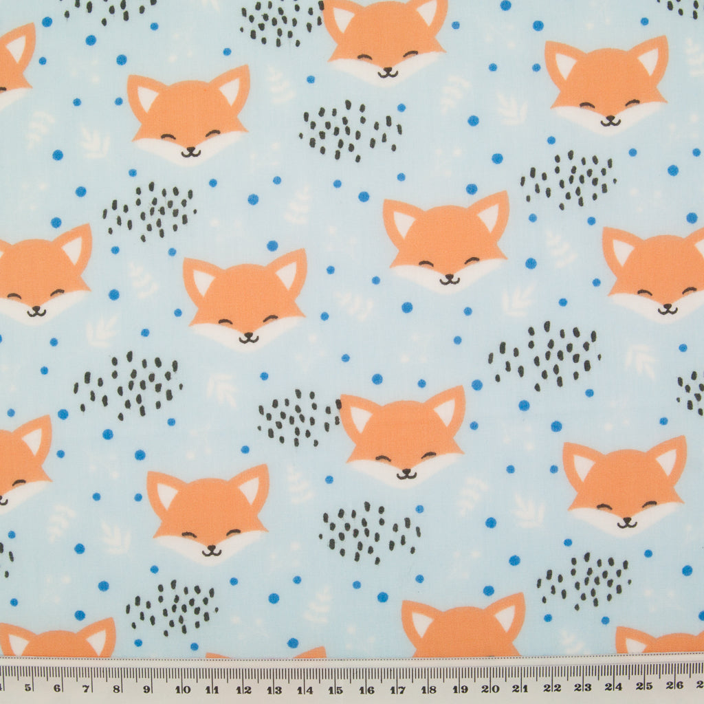 Smiling fox faces are printed on a sky blue polycotton fabric with a ruler at the bottom for size perspective