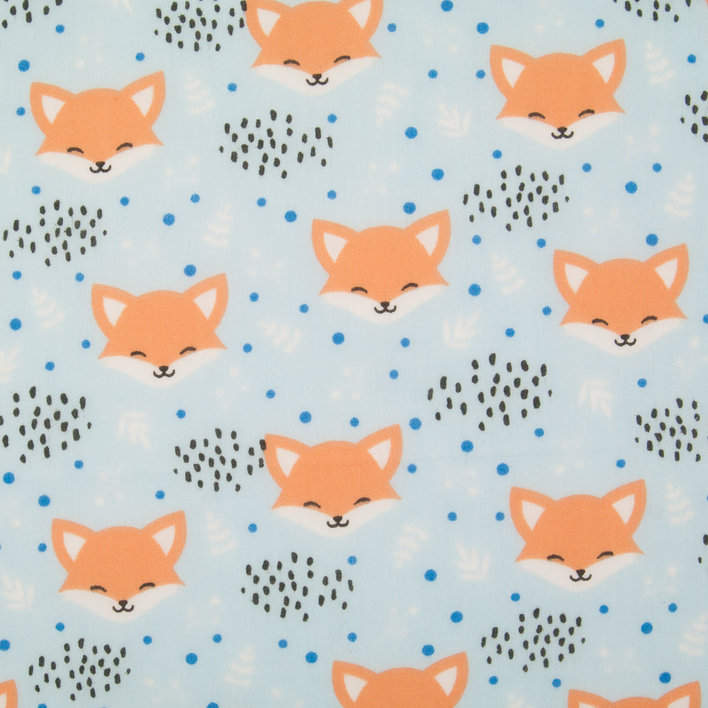 Smiling fox faces are printed on a sky blue polycotton fabric