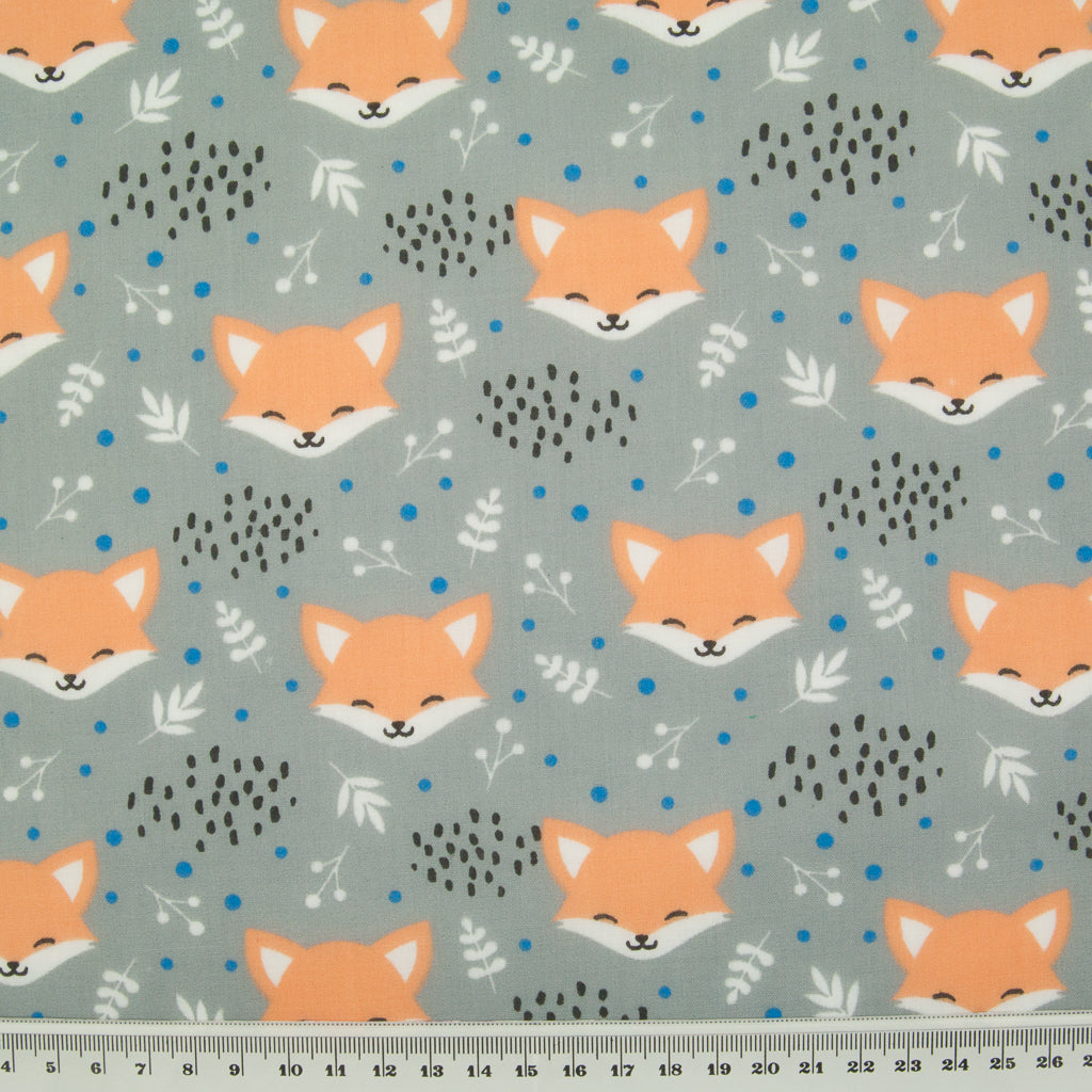 Smiling fox faces are printed on a grey polycotton fabric with a ruler at the bottom for size perspective