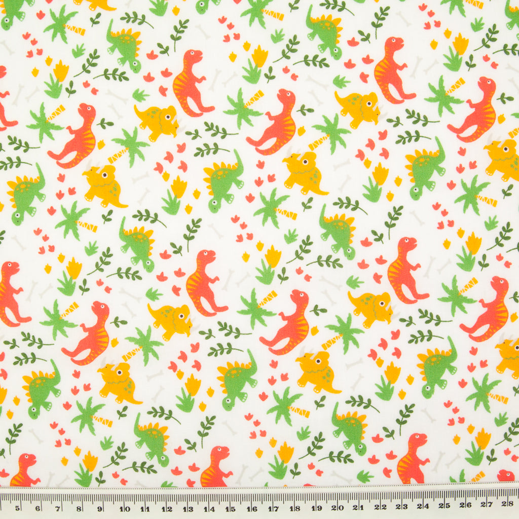 Orange and green dinosaurs are printed on a fat quarter of white polycotton fabric pictured with a ruler at the bottom for size perspective