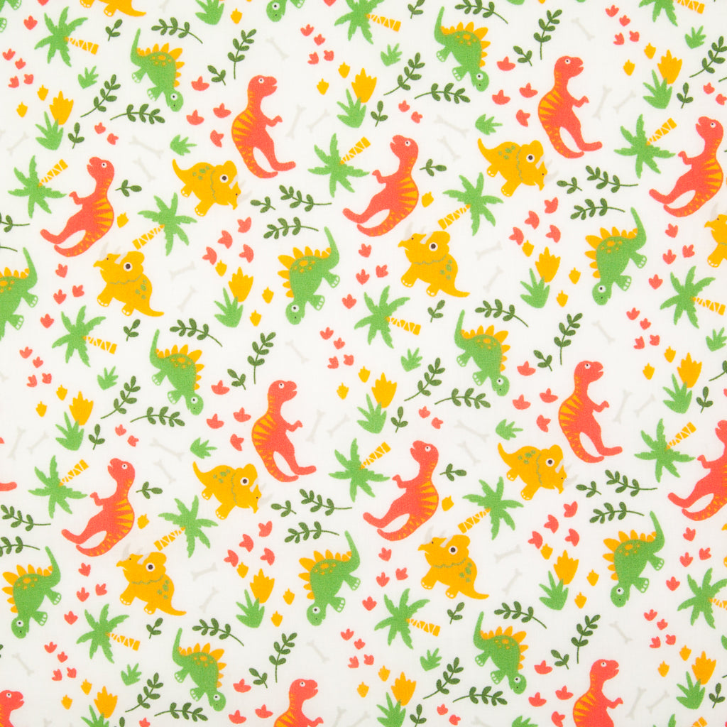 Orange and green dinosaurs are printed on a fat quarter of white polycotton fabric