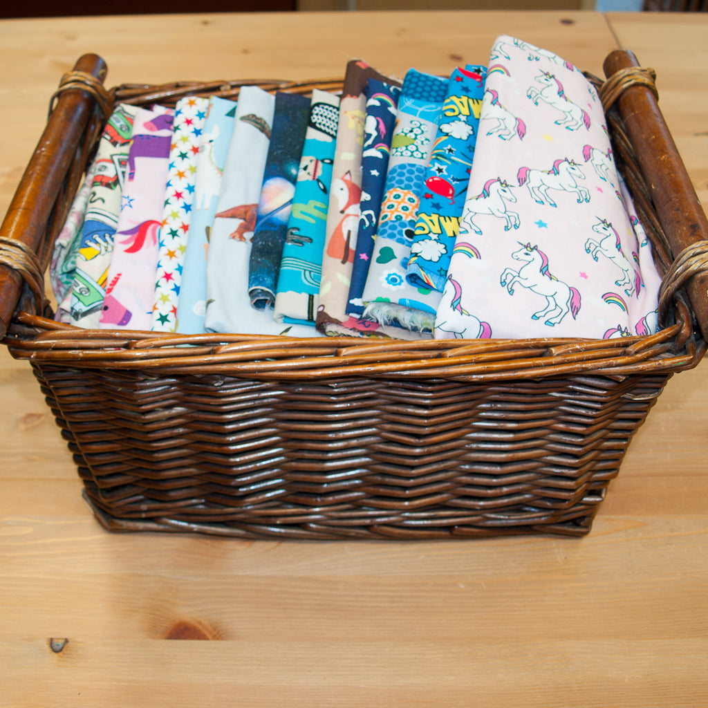A wicker basket containing remnant pieces of children and kids printed cotton fabric