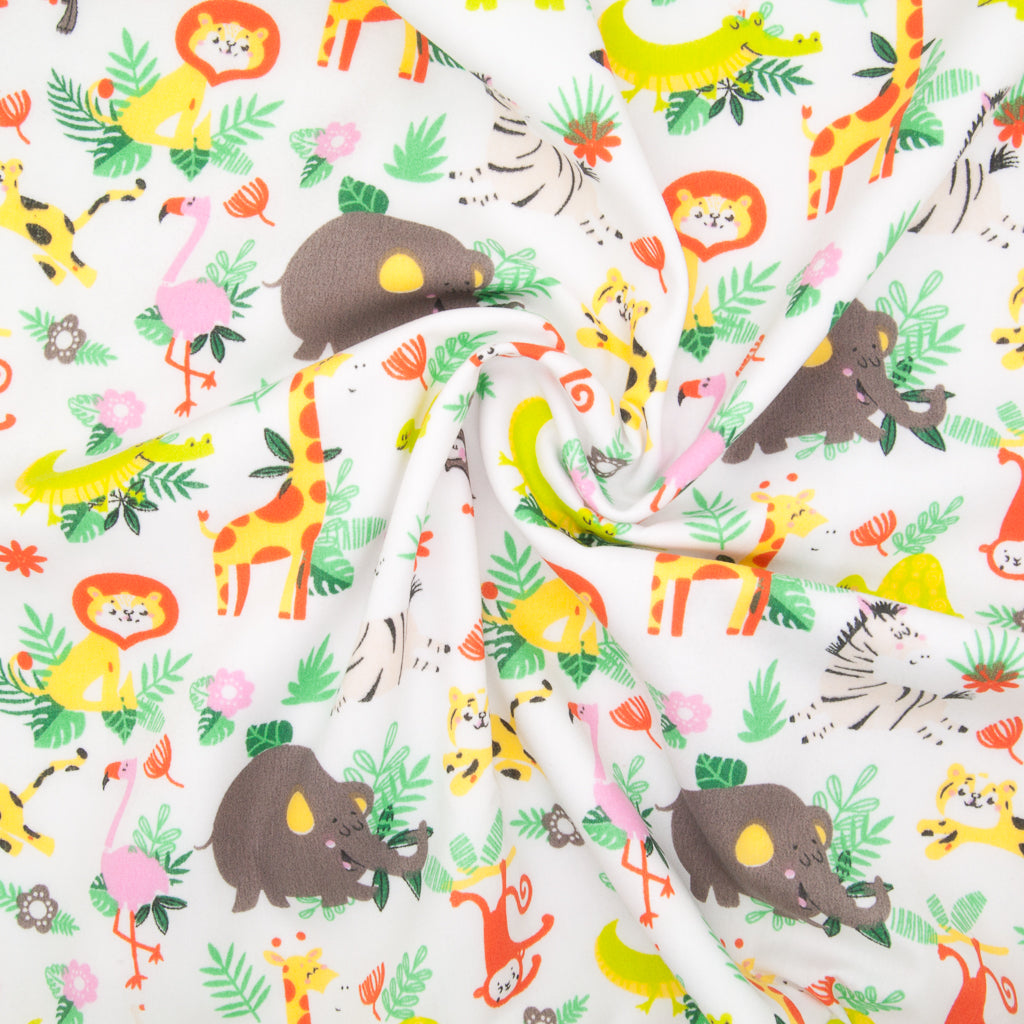 White zoo animal polycotton fabric print with elephant, flamingo, monkey, zebra, lion and giraffe with green foliage in a swirl