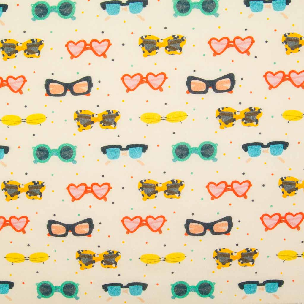 Different shaped sunglasses in green, red and yellow colours on a beach coloured 100% cotton fabric by Little Johnny