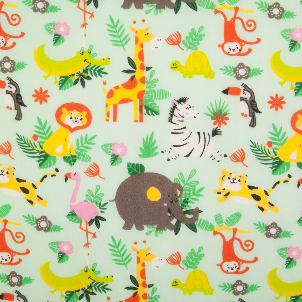 Mint coloured polycotton fabric picturing elephants, giraffes, lions and flamingos in green foliage