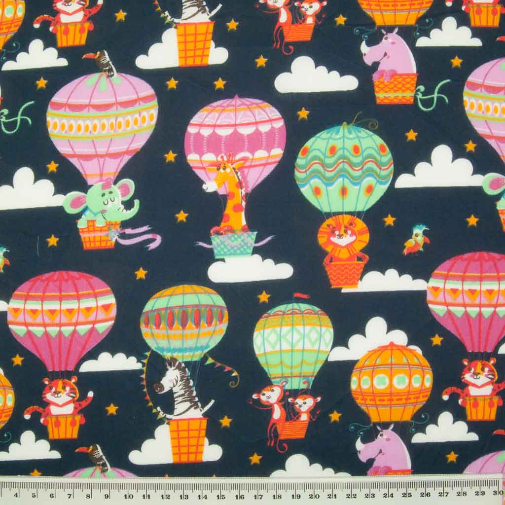 Elephants, giraffes, lions and zebras float away on hot air balloons printed on a navy polycotton fabric with a ruler for size perspective