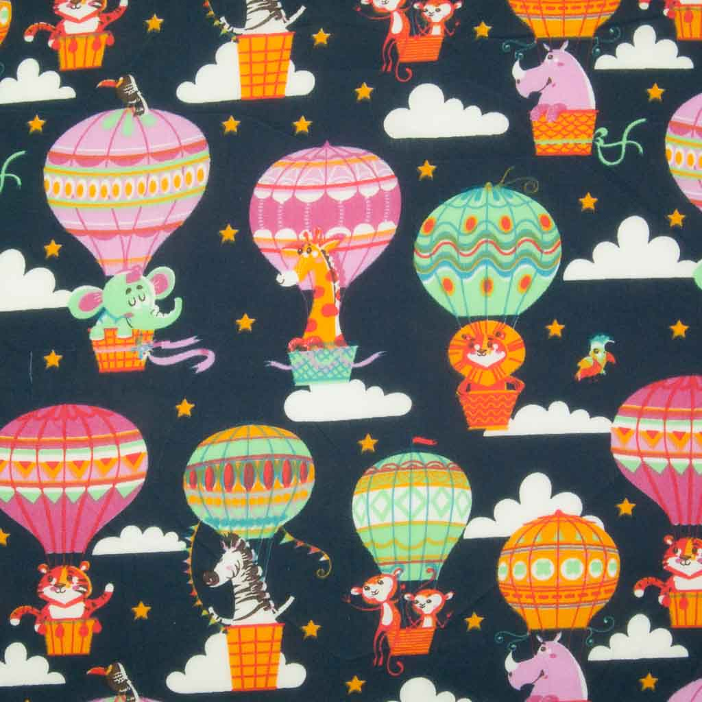 Elephants, giraffes, lions and zebras float away on hot air balloons printed on a navy polycotton fabric