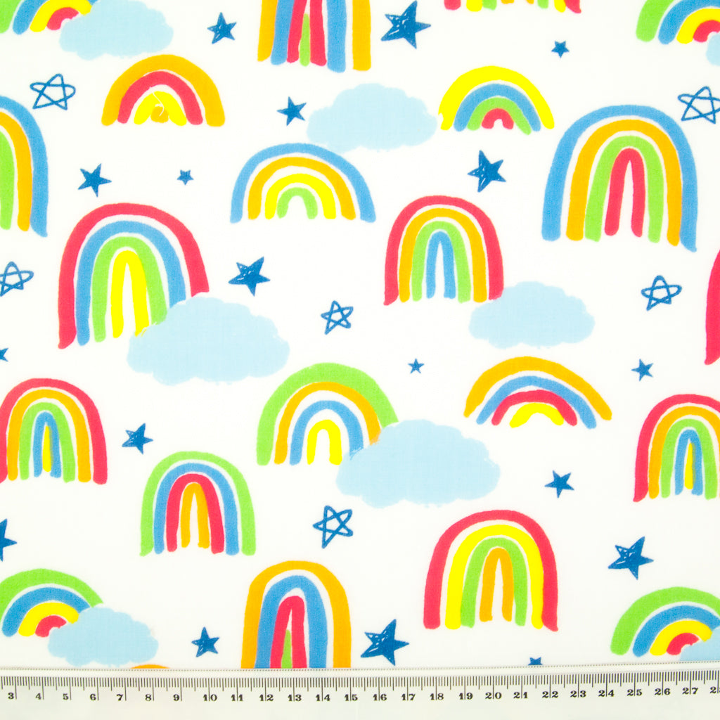 Brightly coloured childlike drawings of rainbows on a white polycotton fabric with a ruler at the bottom for size perspective